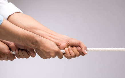 Hands of people pulling the rope: cooperation concept