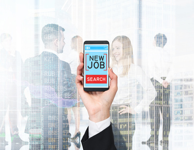 "A hand holds a smartphone with the text ""new job search"" on the screen. A business couple in blur is on the background."