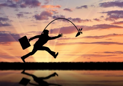 Silhouette of businessman running for the carrot and reflection in water. Concept of money and business