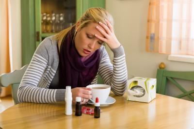 Frau im Krankenstand mit Tee und Medikamenten. Erkältung, Schnupfen und Grippezeit
